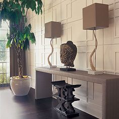 how cool is is this wall? Console table, wavy box lamps and dark wood floors! gray white black entrance colors.