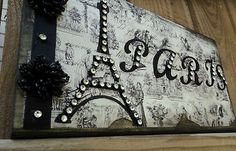 """PARIS Decor Sign Decorative Eiffel Tower in Paper French Decor  C'EST TELLEMENT BEAU   IT IS SO BEAUTIFUL   Unique Vintage Look Paris Eiffel Tower with the word PARIS in a Custom wood block. Embellished with sparkles and ribbon.This is so cute and looks wonderful stand in any part of your home .The artwork is mounted on a 1"""" piece of wood and has a wonderful vintage feel with distressed edges measures The Eiffel Tower 5""""x10"""".   Just perfect for that girly French themed room."""