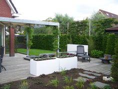 Strakke moderne tuin. Witte bloembakken, houten vlonder, terras overkapping en een vijver met een uniek water ornament.