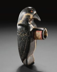 "MISSIPPIAN STONE EFFIGY PIPE    in the form of a bird, finely carved with the wings held tightly to the body, the head with curving beak, and pointed eye rims inset with red beads, surmounted by a tall, cylindrical bowl affixed with an old label reading: ""Steatite Bird Effigy Pipe Wayne County Kentucky.""     length 6 1/2 in."