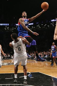 Jrue Holiday #11 of the Philadelphia 76ers scorres as Andray Blatche #0 of the Brooklyn Nets is called for a foul at Barclays Center on December 23, 2012 in the Brooklyn borough of New York City.