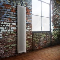Love how this vertical white column radiator looks on the exposed brick wall