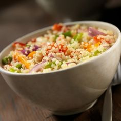quinoa, beans, onions, and tomatoes in a white bowl with a silver fork to the right of the bowl on a brown background