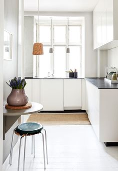 Minimalist kitchen with an artsy touch in the form of clay pottery and a cork pendant lamp. Copenhagen, Denmark apartment of Simone Lone Okholm.