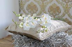 stilleven: witte orchidee (phaleonopsis) op een goudkleurig sfeerkussen.