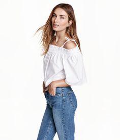 Weiß. Weite, schulterfreie Bluse aus Baumwollstoff. Die Bluse hat oben einen Gummizug und schmale Träger mit Schleife. Kurze, weite Ärmel.