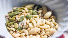 Pinoli, mandorle e semi di zucca e di lino per pesto vegano di basilico