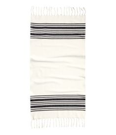 Beach towel in woven, textured cotton fabric with printed stripes. Fringe on short sides and hanger loop on one long side.