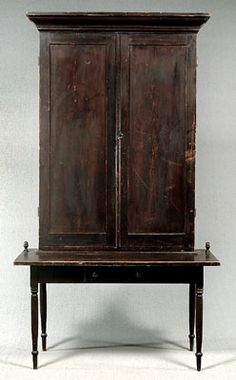 """....maybe..... Two-piece pine plantation desk, top with ogee molded cornice above two frame-and-panel doors, coved bed molding, interior with extensive grooves for compartments, possibly for storing mail or receipts, number from 1 to 280, possibly early post office piece, base table with turned legs, nailed drawer, cut nails, old black paint probably original, each side of top with doorstops shaped as acorns, found in rural Virginia, 93 x 52 x 27"""""""