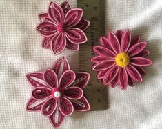 3 white and raspberry colored paper quilled flowers, sealed with paper sealer, with a magnet on back sides.