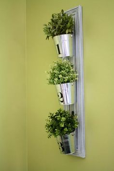 This indoor vertical garden is constructed using only four basic materials: a cabinet door, hooks, a saw tooth hanger, and some pretty tin buckets.  Get the tutorial at Room*6.