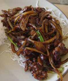 Mongolian Beef - a dish served in Chinese-American restaurants consisting of sliced beef, typically flank steak, and stir-fried with vegetables in a savory brown sauce.