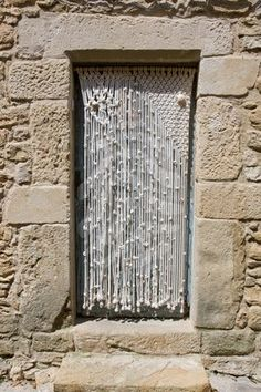 Macrame doorway curtain in an old stone house  Author: Lagui; via http://smittenbyaknot.com/category/vintage/