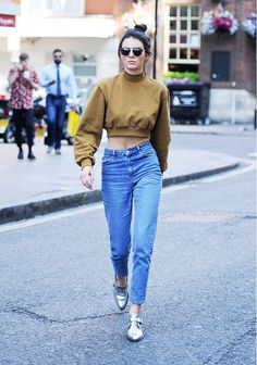 Kendall Jenner wears a cropped sweatshirt, high-waisted jeans, metallic oxfords, and Dior sunglasses