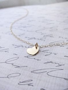 Tiny Heart Disk necklace by Olive Yew is adorable in gold, silver or rose gold. You can also customize by adding an initial. #giftidea