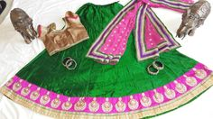 Green raw silk lehnga with a wide pink silk border with gold and white embroidery, with a gold designer blouse and a pink embroidered georgette duppata