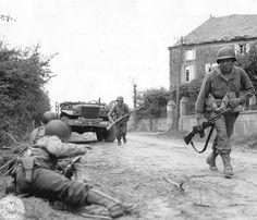 Des soldats du 314th Inf. Rgt de la 79th Inf. Div. ; US de lancent à l'assaut du bourg de La Haye du Puits tout proche. Ils sont sur la route de Bolleville-Barneville, à l'entrée nord-ouest de la ville, près de la maison Lesage qui avait été occupée par les Allemands