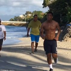 Manchester United striker Anthony Martial runs up and down the beach as he works on his fi...