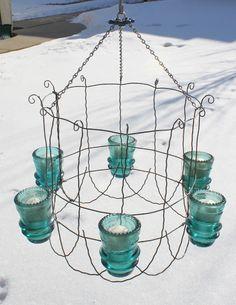 Outdoor chandelier.  Glass insulators and old garden fence!