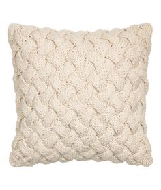 Cable-knit cushion cover with a cotton weave back and concealed zip.