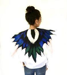 Hand felted Magpie feathered cape in beautiful tones of green blue Merino wool contrasting with the distinctive black and white of the bird. The wings are held together at the front with a hook and eye closure adorned with real natural white feathers with a black felted bobble. Feather Cape, A Hook, White Feathers, Black Felt, Magpie, Larp, Wearable Art, Merino Wool, Handmade Gifts