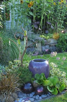 Love the large pot with the globes in this garden!