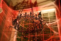 halloween chandelier: hula hoop, twigs, black pvc pipe, flicker lights, black plastic chain and lots of black spray paint. use a socket conversion to attach it to your overhead porch light. Halloween Carnival, Halloween Signs, Halloween Birthday, Halloween Projects, Holidays Halloween, Halloween Crafts, Halloween Decorations, Halloween Ideas, Voodoo Halloween