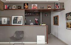 """""""A moldura de imbuia cobre o balcão, entre a sala e a cozinha, e segue como prateleira pelas paredes. """"Como o morador tem muitos quadros, pode apoiá-los nela e trocá-los à vontade"""", diz o arquiteto Gustavo Calazans. Dentro da cozinha, também há obras.""""Mais no Casa&Jardim"""
