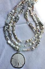 Genuine Florida sand dollar pendant hanging on a triple strand of white beads