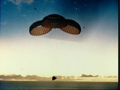 """May 26, 1969. Apollo 10 command module """"Charlie Brown"""" descends for splashdown in the Pacific Ocean. On board are astronauts Thomas P. Stafford (commander),   John W. Young (command module pilot), and Eugene A. Cernan (lunar module pilot). Image: NASA KSC 10075167"""