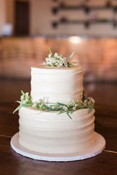 Such a simple design yet so pretty! White frosting topped with small white flowers makes this cake by Sweet Treets Bakery almost almost too pretty to eat! Photographed by Joshua Aull Photography. Boho Glam Austin Wedding from Altar Ego Weddings | Jaime + Matt #sweettreetsbakery #alteregoweddings