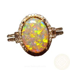 A beautiful Opal ring with a gem quality Coober Pedy Dark Crystal Opal that has a stunning mix of colors.  The 2.2 carat Opal is full of bright colors and is accented with a halo of small quality Diamonds.  The Diamonds continue down the band with a Baguette Diamond accent on the top of each band
