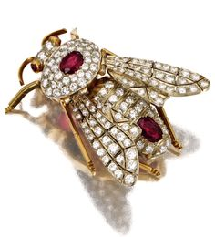 DIAMOND AND RUBY BEE BROOCH The realistically modelled insect with articulated wings set throughout with 130 round diamonds weighing approximately 3.75 carats, the body and tail accented with 2 cushion-shaped rubies, the eyes with cabochon rubies, mounted in yellow and white gold, brooch fitting detachable.