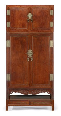Rare Chinese huanghuali compound cabinet, 18th century. The rectangular cabinet with wide double doors constructed with recessed panels, two interior drawers, conforming top section and simple bronze hardware; with shaped and detailed apron; wholly constructed from richly-grained and colored huanghauli; with rare two-drawered huanghuali stand. #FreemansAuction
