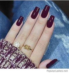 Long burgundy gel nails with gold rings