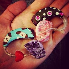 Phonak hearing aids with pink and purple swirl ear molds and stickers