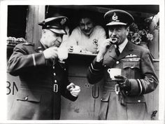 1943- Brig. Gen. Robert Candee, commanding general, Eighth Air Support Command, and Vice Air Marshal J.H. D'Albiac, of R.A.F. Fighter Command, get donuts and tea at an American Red Cross Mobile Unit.
