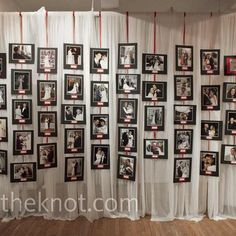Matted photos attached to ribbon and hanging against a curtain backdrop. Very cute for displaying old wedding photos of your guests or photos from the bride and groom's childhood.