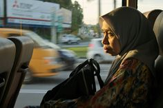 An old muslim woman taking a ride in a bus. Old and tired; yet she struggle on. This photo was taken in a rapidbus KL in Shah Alam, Selangor.