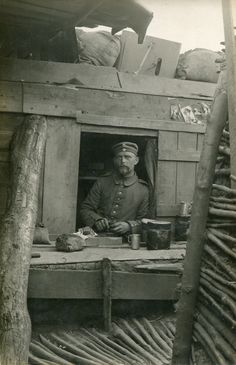 """German soldier eating a meal from a dugout window platform. Note the """"girlie"""" pictures overhead as well as the """"Grabenschild"""" (trench shield) on top of the revetment."""