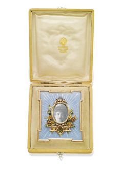 THE PRIVATE COLLECTION OF PRINCESS KATHARINA HENCKEL VON DONNERSMARCK: AN ANTIQUE GOLD AND ENAMEL FRAME, BY FABERGÉ, WORKMASTER VICTOR AARNE, CIRCA 1890. The central oval frame atop a bi-coloured gold architectural plinth, surmounted by a rose gold ribbon and bordered by coloured gold garlands, to the pale blue guilloché enamel frame of rectangular stepped-corner outline and silver-gilt.