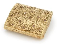 "A 14 KARAT GOLD AND RUBY ""OSTRICH SKIN"" COMPACT, RETAILED BY TIFFANY & CO., NEW YORK, MID 20TH CENTURY chased to simulate skin, the raised dots of the cover set with rubies marked on flange Germany, Tiffany & Co., 14Kt, EB, and 585."