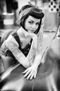 Rockabilly pinup sitting in car with head scarf and overalls