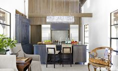 "In a natural and modern Sonoma house, the steel island is topped with Pietra Grigia granite set into a metal frame. Barstools by Holly Hunt. Custom light fixture. A recessed oak cabinet was wire-brushed and stained black to echo the gunmetal finish on the island. ""I like to use black in all my interiors,"" says designer Rela Gleason. ""It's like an exclamation point."" David Tsay  - HouseBeautiful.com"
