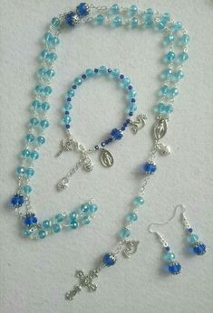 Rosary five decade using 8mm turquoise ab glass faceted crystals accented with dark blue 10*12 crystals and tibetan silver finish with one decade matching bracelet and earings. Specially commissioned gift