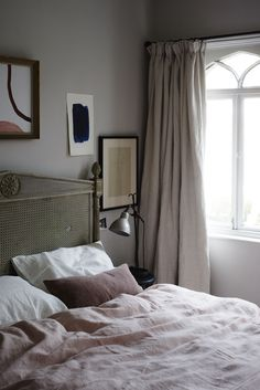 """One place not to go bare in the bedroom: the windows. """"A great trick to make the room look bigger is to have curtains in a very similar shade to the walls,"""" Hutchinson says. """"If you've used a tight color palette, then you can also play with texture. Ours are made from a beautiful soft washed linen by the Designers Guild; they're Brera Lino in Parchment."""""""