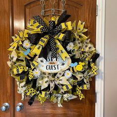 """Welcome your guests with this beautiful Bumblebee deco mesh wreath. This wreath is made on an 18"""" wire frame using yellow, black and iridescent yellow deco mesh. The finished measurements are 30"""" x 30"""". The wreath is embellished with streamers. Each streamer is finished with a bee or bee hive button in the center, giving it extra detail. In the center is the bee our guests metal sign. Featuring 2 wooden bees. The top of the wreath is embellished with a large bow."""