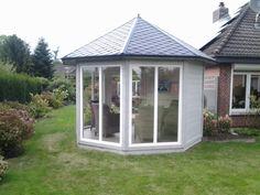 Gartenpavillon in Grau und Weiß mit bodentiefen Fenstern.