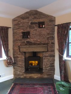 Woodwarm stove in a traditional stone fireplace, stove installation by Kernow Fires in Cornwall. #woodwarm #stove #multifuel #freestanding #fireplace #traditional #mantle #hearth #kernowfires #cornwall #redruth #wadebridge
