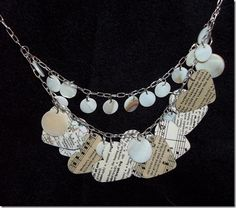 A heart necklace… I started with some sheet music, a few pages from an old dictionary, an old map, some scrapbooking paper, Mod Podge, small flat shell beads and a few bigger ones, some necklace chain....